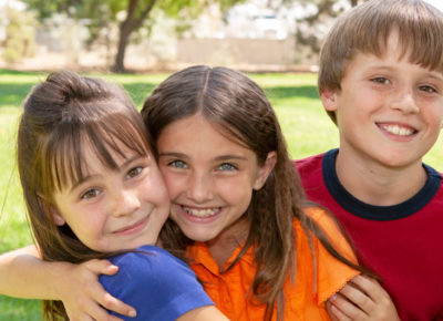 Three preteen kids huddle in a group hug as they play outside.