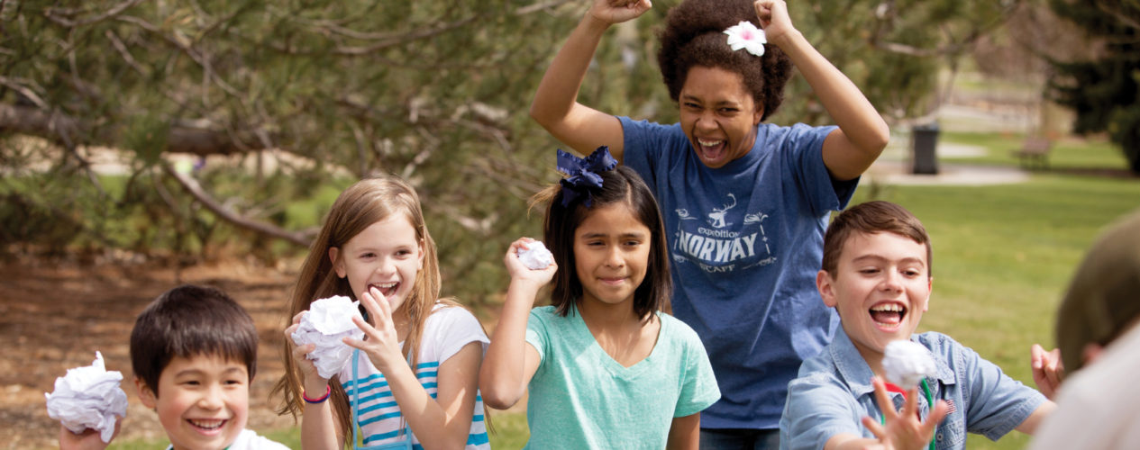 A children's ministry volunteer cheers excited as her students through crumbled paper balls away.