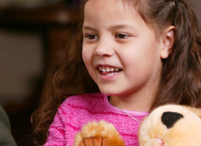 An elementary girl is holding an encouraging prayer bear.