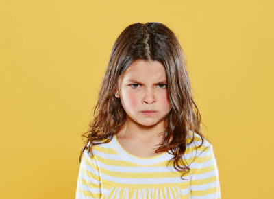 A girl wearing a yellow striped shirt is standing in front of a bright yellow background. She looks like she is one of those children with negative attitudes.