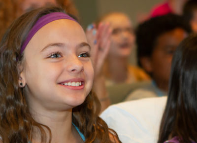 A preteen smiling during a lesson on missions.