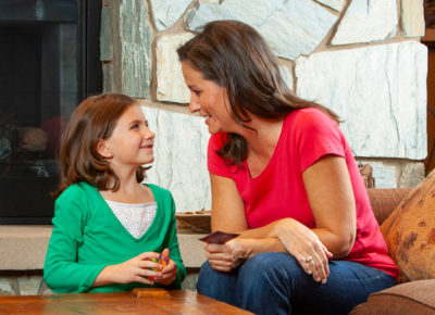 A mom sits in front of a fireplace with her elementary-aged daughter. They are talking and laughing as they get ready to use the encouragement web with the rest of their family.