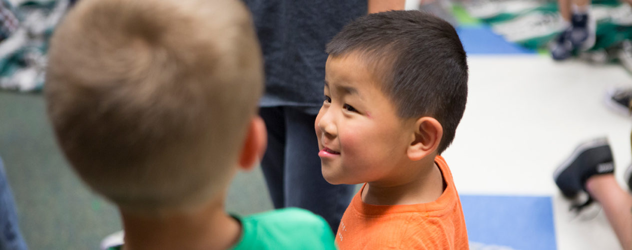Two preschool boys look at each other during a lesson on thankfulness for our bodies.