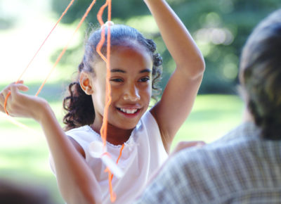 Preteen girl with raised arms trying to untangle from orange yarn