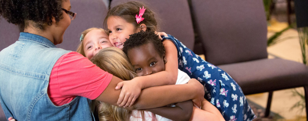 A group of four elementary children hugging their small group leader.