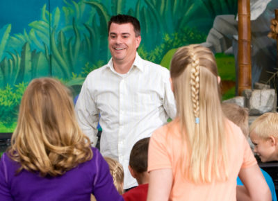 A male pastor is standing in front of a large group of kids. He's engaging them in an activity.