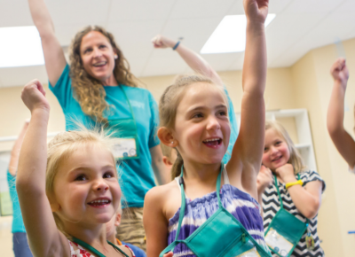 Preschool-aged-girls with a hand raised in celebration. VBS leader in the back of the group raising her hand, too.