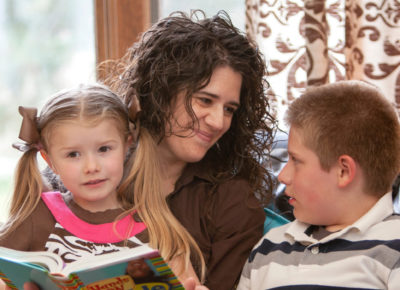A mom reads the Bible with her two children, a preschool girl who is sitting on her lap and a preteen boy who is sitting next to her.