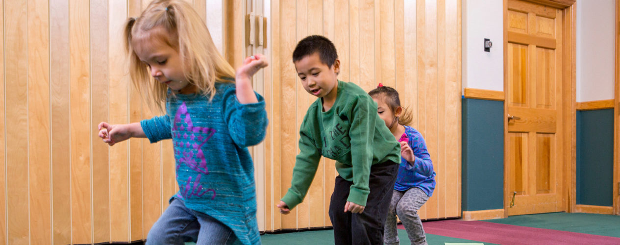 Three first-graders hop from one side of the room to another.