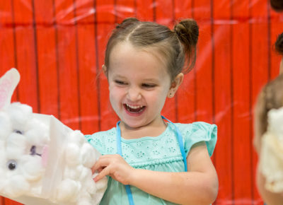 A preschool girl smiling excitedly as she plays with a puppet.