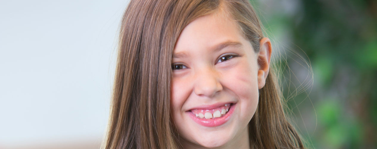 A preteen girl smiles during a lesson on spending time with God.