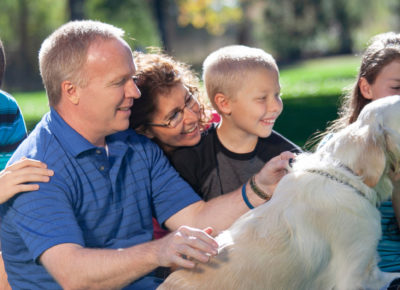 A family with a dad, mom, and three kids sitting outside on the grass. They are petting a yellow lab.