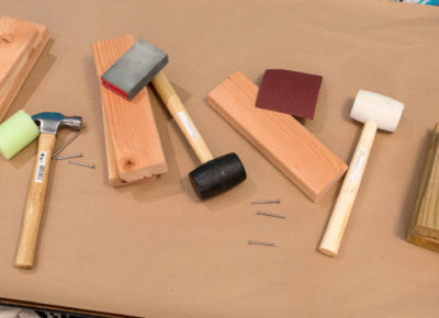 A father's day event table that has a variety of construction tools on top of a piece of cardboard.