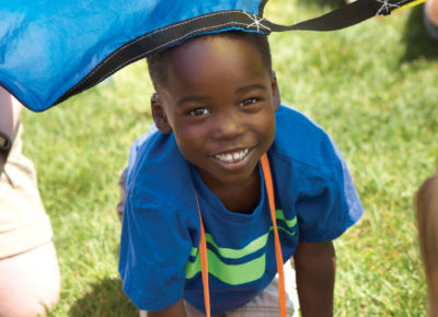 An elementary-aged VBS visitor is crawling out from under a colorful parachute. He's smiling!