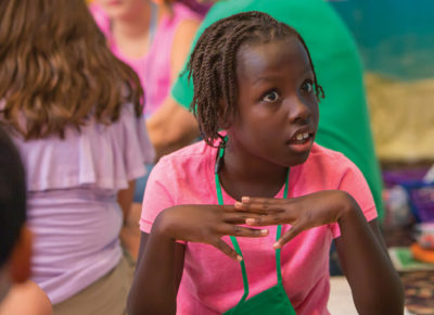A elementary girl looks shocked during a lesson about the woman at the well.