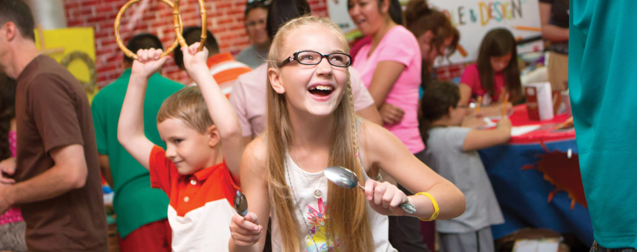 An older elementary aged girl is smiling as she and her brother sing and dance at a fall fest. She is holding a spoon in her hand that she was using as a musical instrument.