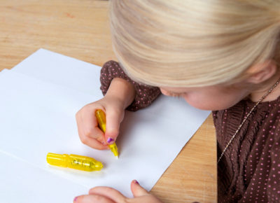 Elementary-aged girl writing on a white sheet of paper.