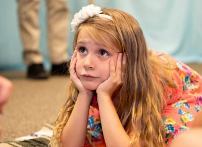 Elementary aged girl is resting her chin on her hands as she leans forward on the ground.