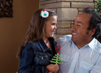 Dad and daughter smiling as the daughter holds a Christmas tree ornament made of popsicle sticks.