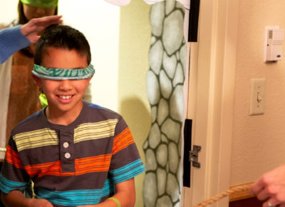 A preteen boy in a polo with large, colorful stripes is blind-folded as he walks through a door.
