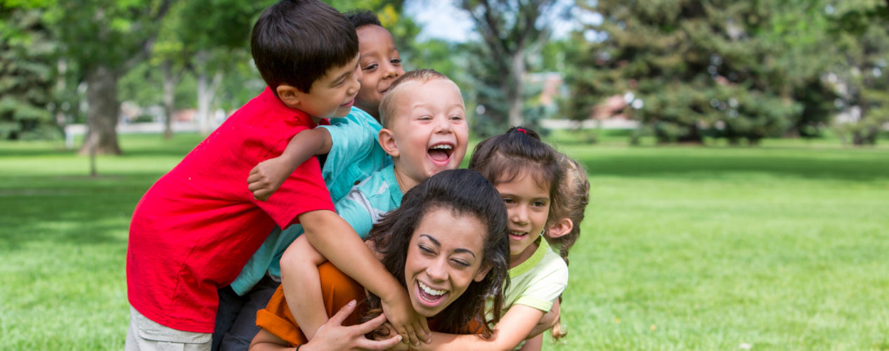 A group of four children laughing as they climb on their children's ministry volunteer.