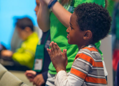 Elementary-aged boy prays during a large church service.