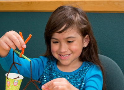 An elementary girl is sitting at a table making a wind chimes.
