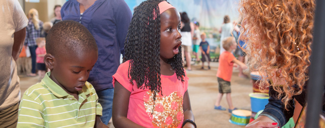 Two elementary aged kids participating in a church's special event. The girl, who is older, looks in awe over the activity.