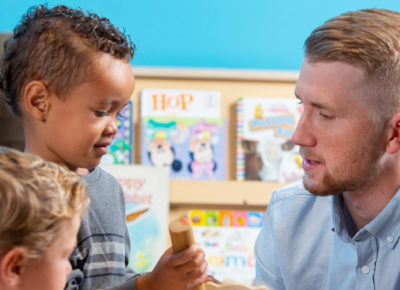 Male volunteer works with two preschool aged boys in his Sunday school class.