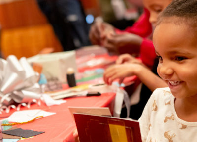 Preschool girl smiles as she sits at a table of crafts.