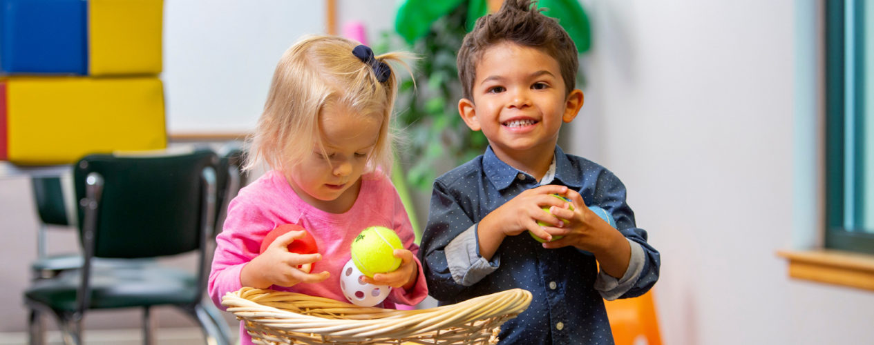 Two Toddlers Grabbing Toys Out Of A Basket