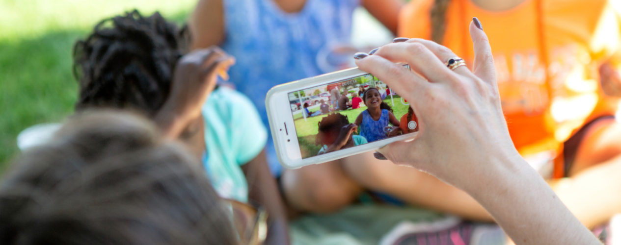 A volunteer holds a phone as she takes a goofy picture a group of preteens.