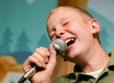 A boy single Christmas carols into a microphone.