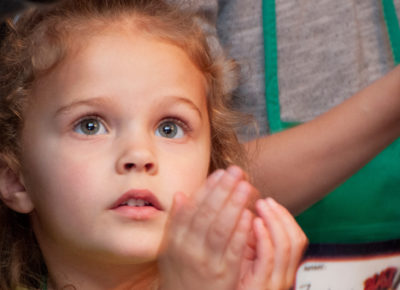 A young elementary girl stares in wonder as she cups her hands.