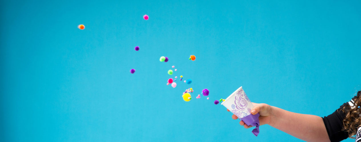 A paper cup with a ballon on the bottom launches colorful pom poms out in front of a bright blue background.