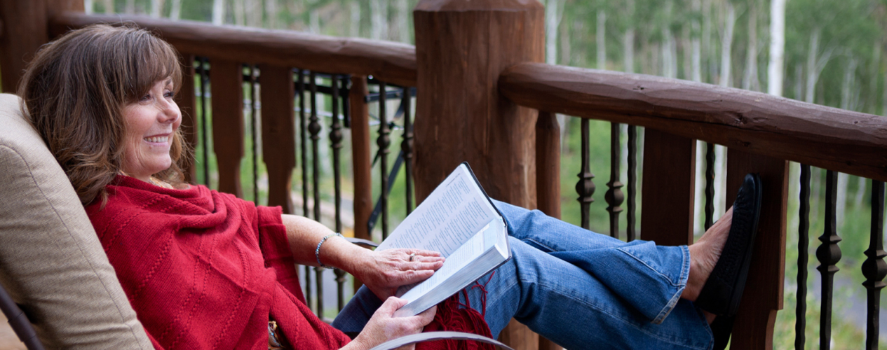 Woman reading her Bible on a patio. She's in a cozy chair with her feet propped up.