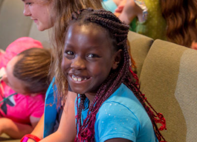 A preteen girl is sitting in a sanctuary chair. She is smiling straight at the camera.