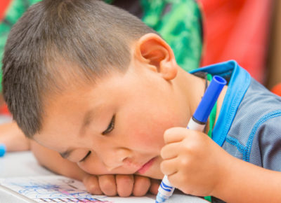 A preschool boy is sadly coloring with a marker. He's working through some grief.