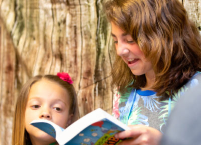 An older elementary girl reading aloud from the Bible to younger kids during a Sunday school lesson.