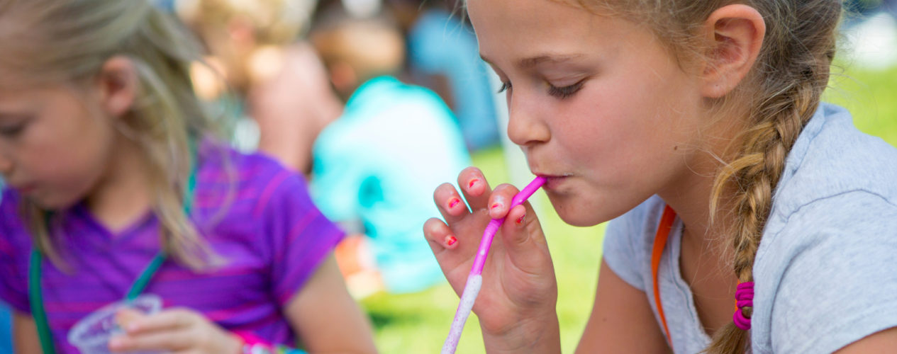 A preteen girl drinking a shake with a straw at a fun family summer night.