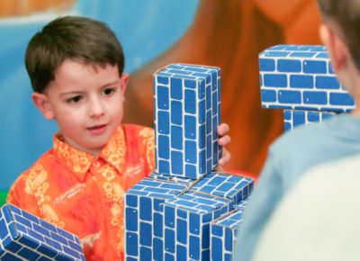 An elementary boy has a look of concentration as he stacks large cardboard building bricks.