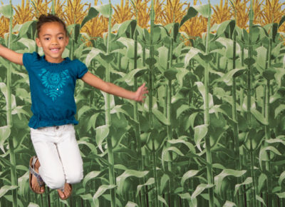 An elementary-aged girl leaps up for a photo in front of a corn backdrop.