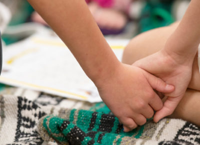 Two children hold hands after witnessing violence.