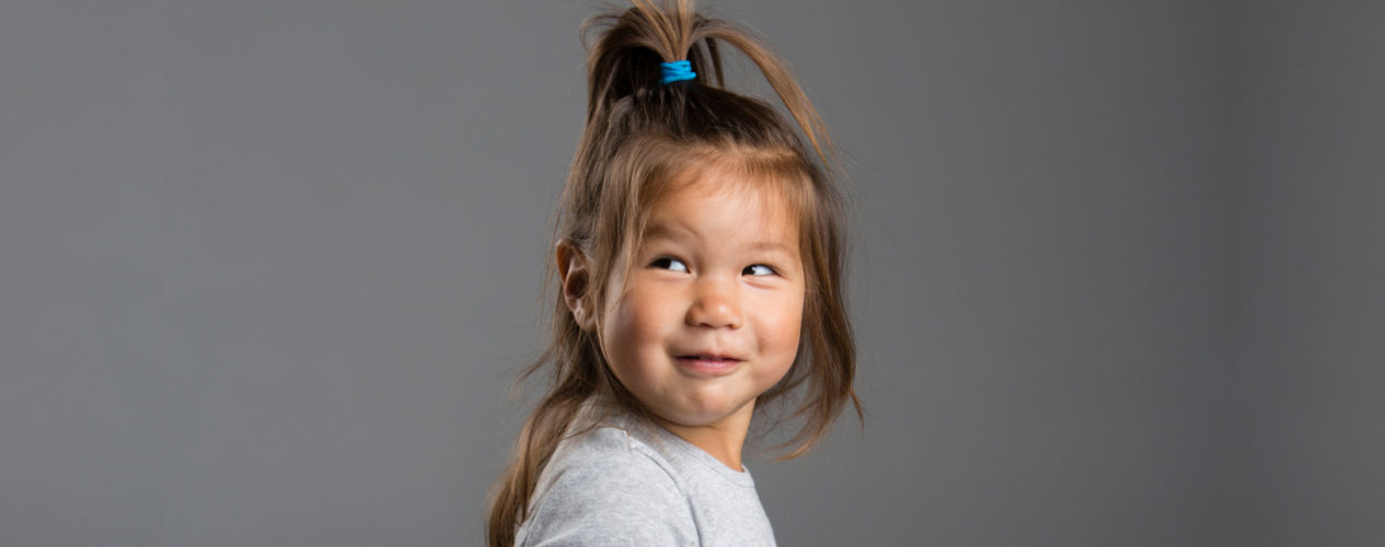 A girl toddler smiles as she looks over her shoulder.