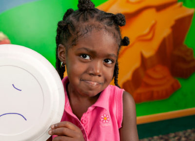 A preschool girl holds up a paper plate with a sad face on it. She's making the same face.