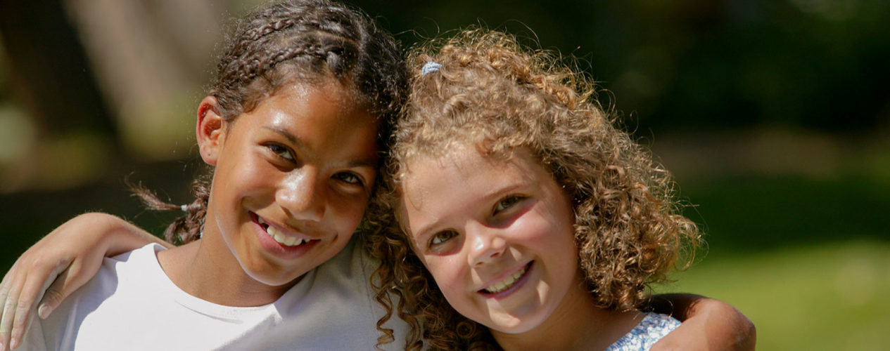 Two preteen girls smiling as they wrap their arms around each other's shoulders.