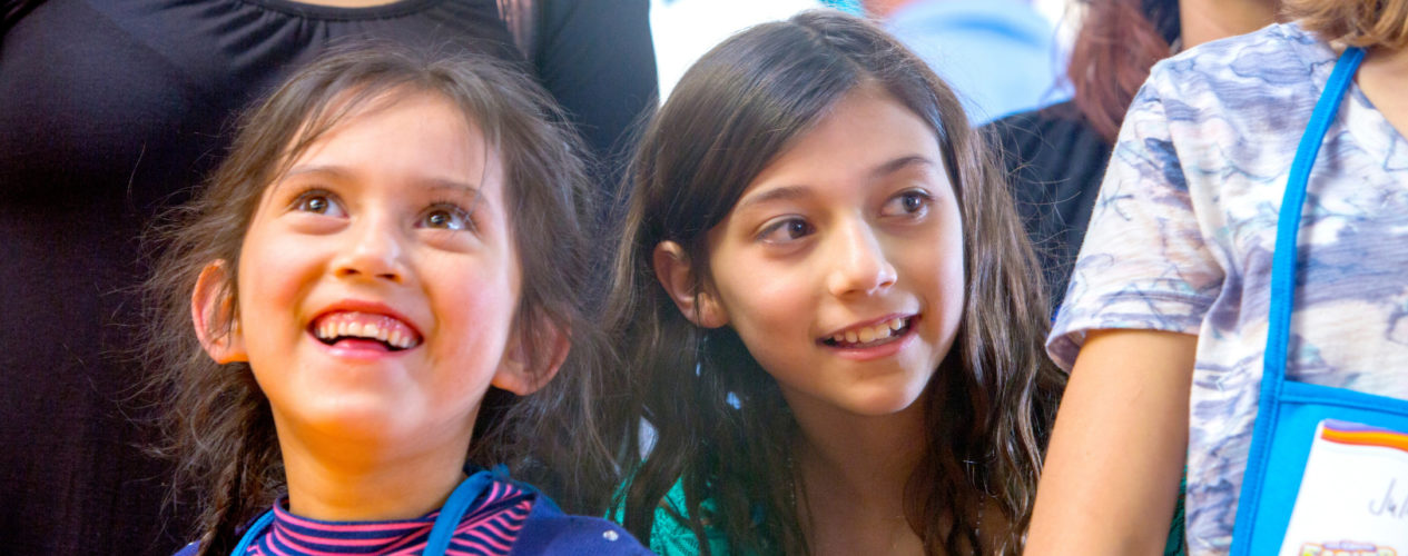 Two elementary girls are smiling as they participate in an Easter idea..