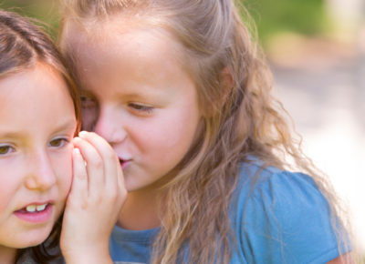 An elementary-aged girl whispering into another girl's ear. She is trying to Peer Pressure her friend.