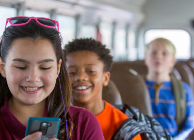 A group of preteens sitting on a bus.