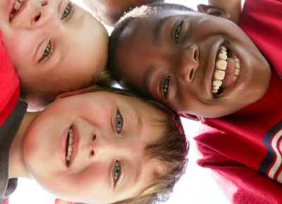 A group of elementary-aged boys huddled shoulder-to-shoulder, looking down at a camera that sits between them. They have huge smiles on their faces.